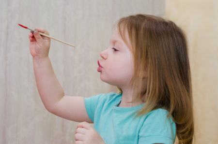 little girl draws with a brush and paints