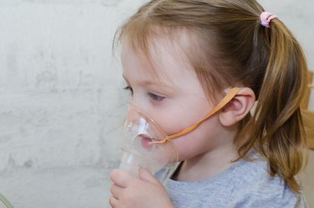 a little girl makes inhalation at home with an inhaler