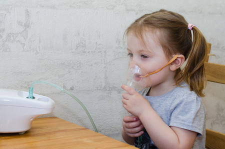 a little girl makes inhalation at home with an inhaler