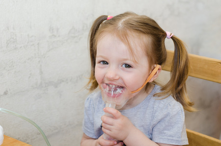 happy little girl makes inhalation at home with an inhaler