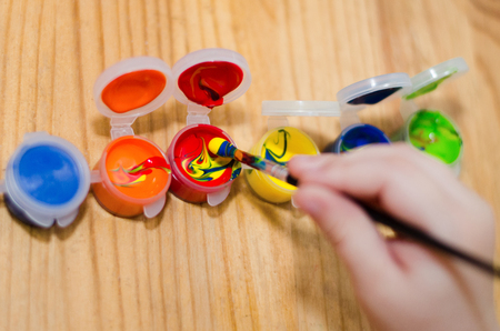 child's hand dip the brush in the paint can