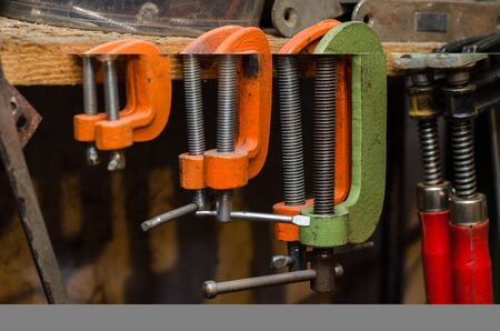 a set of multi-colored different clamps hang in the workplace