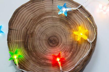 loft background with colored garland stars and round saw cut tree