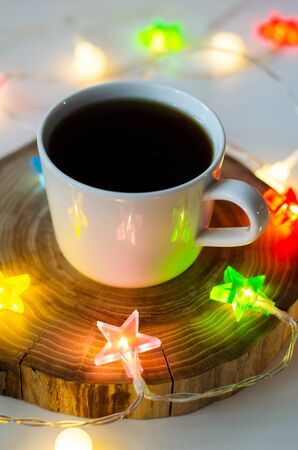cozy still life with a cup of coffee on a wooden stand and colored garlands of stars