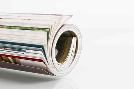Roll of magazine on white background photo