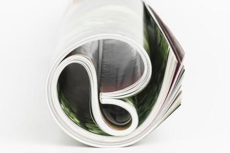 Roll of magazine on white background