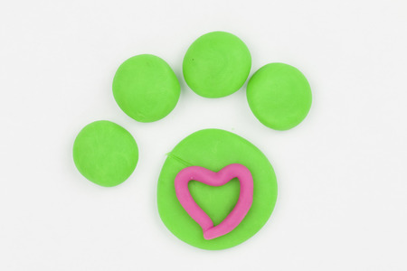 Paw from children bright plasticine - Stock Image macro  Stock Photo