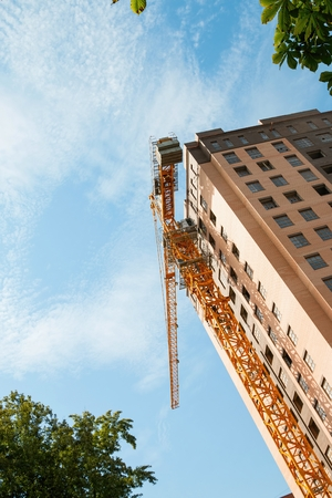 lenina: Rostov - on - Don, Russia - August 27, 2015: Crane and building construction site against blue sky, established in Lenina avenue in Rostov - on - Don. Editorial