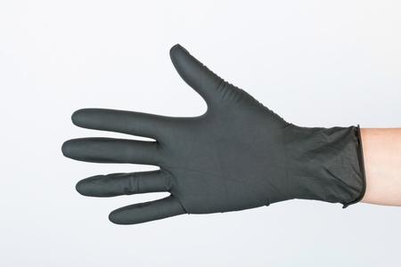 utiles de aseo personal: Mano en guante médico negro. Macro Imagen.