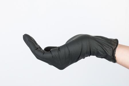 utiles de aseo personal: Hand in black medical glove. Stock image macro.