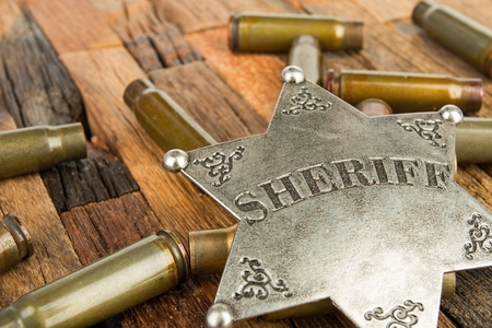 deputy: Sheriff badge and bullets shell on wooden background. Stock image macro.
