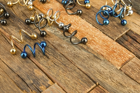 body jewelry: Jewelry for piercing on wooden background. Stock Image macro.