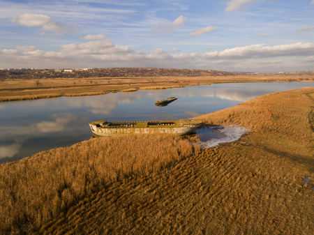 ship wreck: Abandoned broken ship in autumn river. Aerial view.