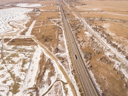 Snowy and frozen winter road with a moving car on it. Aerial view.