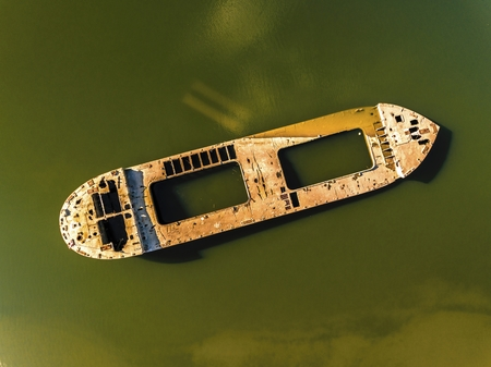 Abandoned broken ship in autumn river. Aerial view.