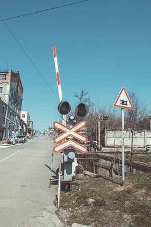 Railway crossing sign with lights underneath. This is for a road traffic and to warn it of when a train is coming.