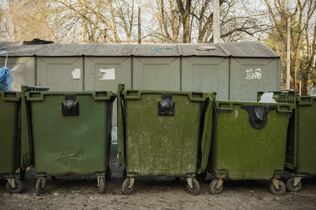 environmental sanitation: Old green dumpsters on the street. Household waste in the city.
