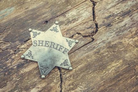 Sheriff badge on wooden background. Macro shot.