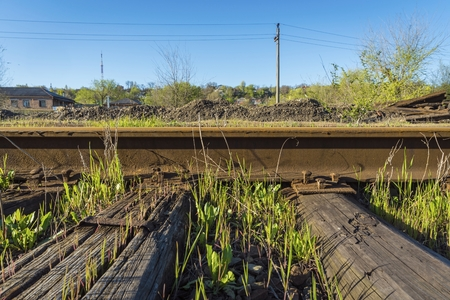 rusty nail: Steel rails bolted down to wooden railroad ties. Old rustic railroad track. Stock Photo