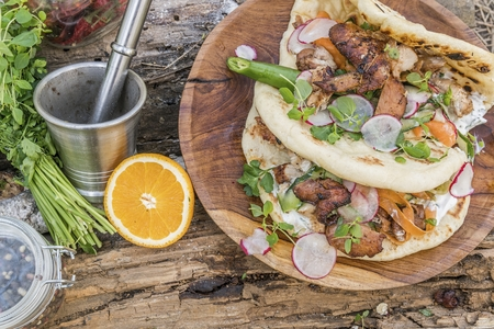Burrito or shawarma with grilled chicken and vegetables on wooden background in forest. Natural healthy food concept.