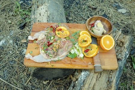 Poulet mariné savoureux et juteux sur une planche à découper. Poulet à la marinade à l'herbe.