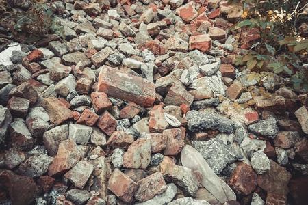 Pile de briques rouge cassées avec des ordures. Image stock.