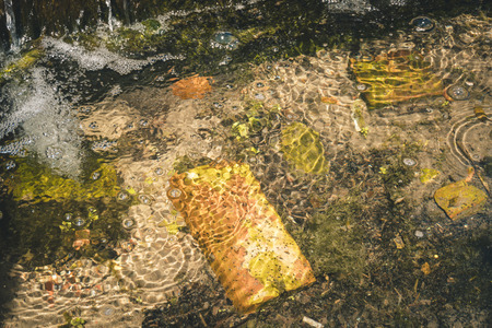 Old red brick and garbage in clear creek water. Water pollution concept.