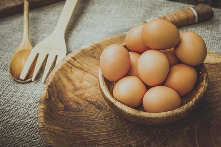 Eggs in a wooden bowl on the table. Natural healthy food concept.