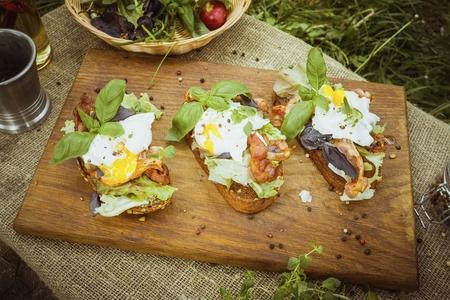 Oeufs pochés, laitue et bacon sur pain grillé. Concept de nourriture saine naturelle.