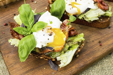 Poached eggs, lettuce and bacon on toasted bread. Natural healthy food concept. Banque d'images