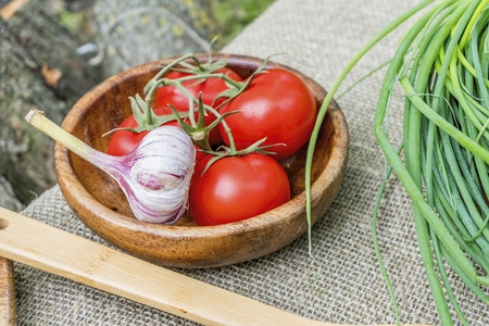 Fresh tomatoes and garlic in wooden bowl. Natural healthy food concept. Banque d'images
