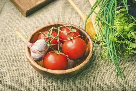 Tomates fraîches et ail dans un bol en bois. Concept de nourriture saine naturelle. Banque d'images