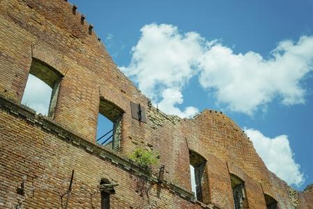 Maison abandonnée, mur en ruine contre le ciel bleu avec des nuages. Image stock. Banque d'images