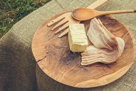 Bacon strips and butter in wooden bowl with cooking utensils. Stock image.