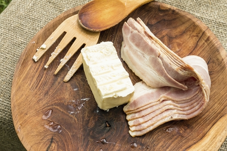 Bandes de bacon et beurre dans un bol en bois avec des ustensiles de cuisine. Image stock.