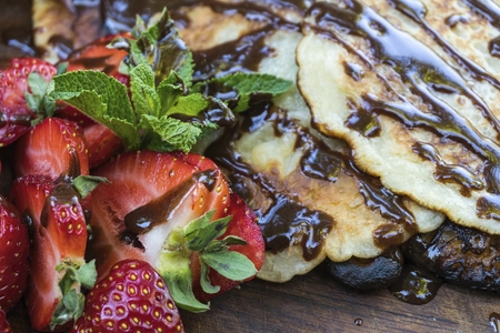 Homemade pancakes with, juicy strawberry, fresh mint and chocolate. Natural healthy food concept. Banque d'images