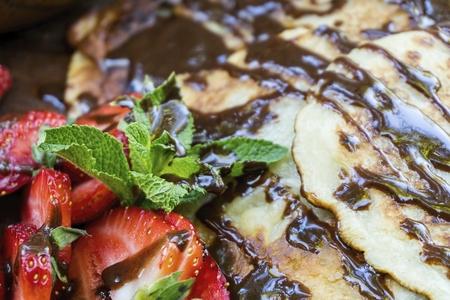 Crêpes maison, fraise juteuse, menthe fraiche et chocolat. Concept de nourriture saine naturelle. Banque d'images - 79704089