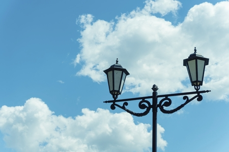 Old lamp post against blue sky with clouds. Stock image.