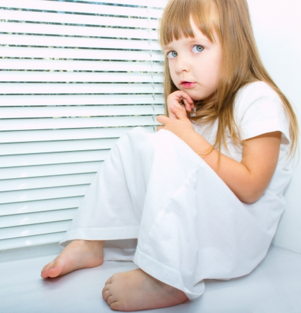 scared child: A little afraid girl is sitting on the window Stock Photo