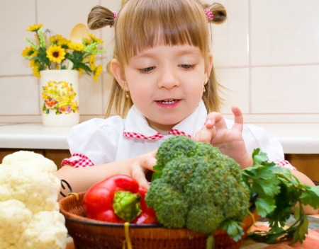 Portrait of a happy little girl with vegetables in the kitchen Standard-Bild