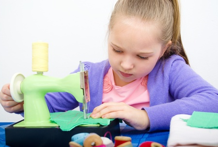 Cute girl sewing on a sewing machine at home photo