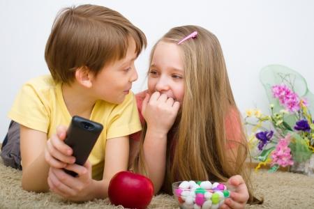 tv panel: Children watching TV  holding  control Stock Photo