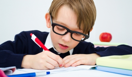 Small schoolboy writing homework from school in workbook photo