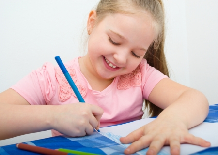 a small painting: Closeup portrait of girl drawing with colorful pencil Stock Photo