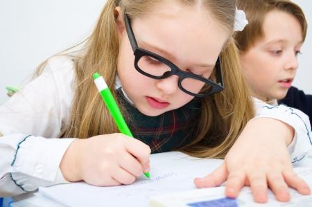 Little schoolchildren writing at school in workbook