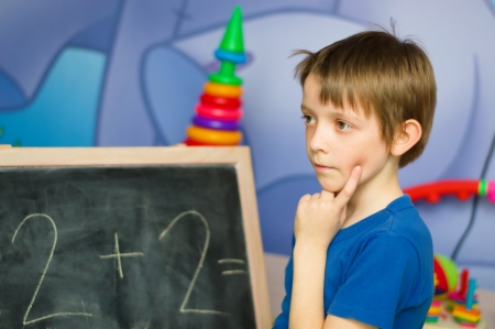 Schoolboy standing by the blackboard being deep in thought photo