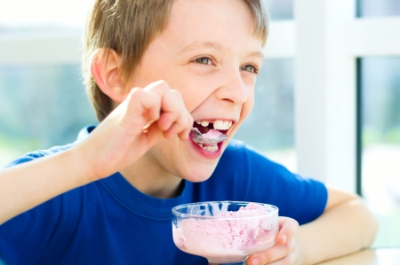 Happy young boy eating a tasty ice cream photo