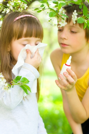 catarrh: Little girl is blowing her nose, brother gives her nasal spray