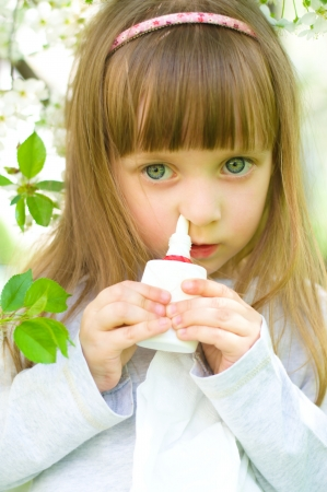 Little girl spraying medicine in nose, nose drops, nose spray.