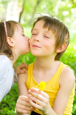 gives: Young girl gives her brother a kiss on the cheek outdoors Stock Photo